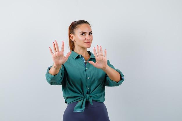Jeune femme en chemise verte montrant un geste d'arrêt et l'air confiant, vue de face.