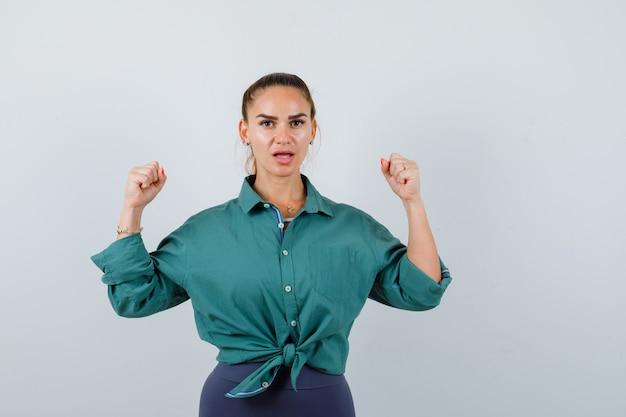 Jeune femme en chemise verte montrant le geste du gagnant et ayant l'air chanceux, vue de face.