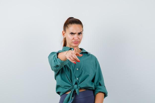 Jeune femme en chemise verte pointant vers la caméra et regardant grave, vue de face.