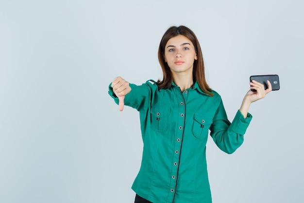 Jeune femme en chemise verte tenant un téléphone mobile, montrant le pouce vers le bas et l'air mécontent, vue de face.