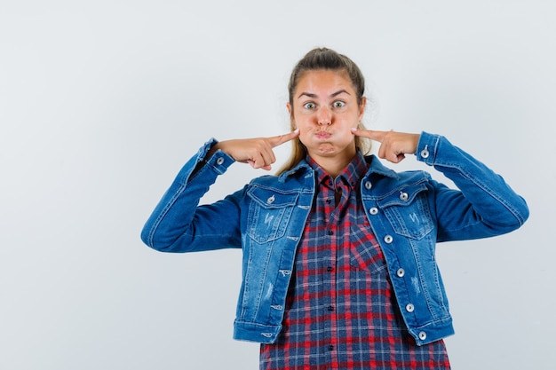 Jeune femme en chemise, veste en appuyant sur les doigts sur les joues soufflées et à la drôle, vue de face.