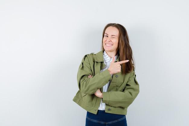Jeune femme en chemise, veste pointant vers le côté droit et semblant confiante, vue de face.