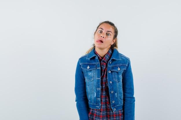 Jeune femme en chemise, veste qui sort la langue et à la drôle, vue de face.