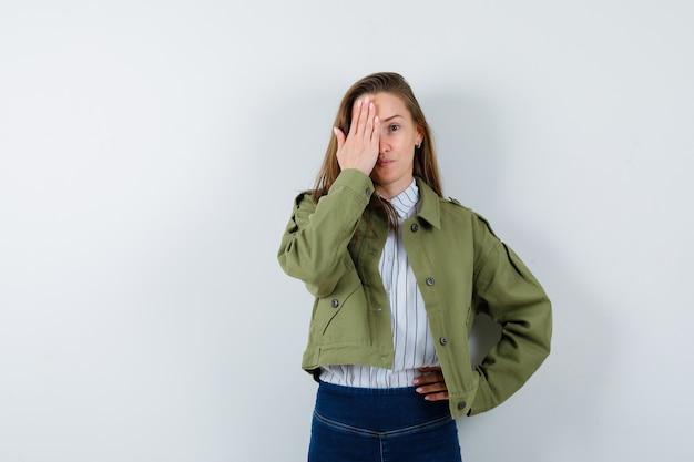 Jeune femme en chemise, veste tenant la main sur l'œil et l'air mignon, vue de face.
