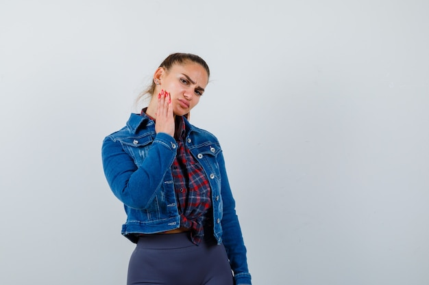 Jeune femme en chemise, veste touchant sa joue et regardant vers le bas, vue de face.