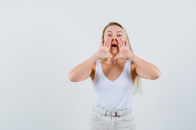 Jeune femme en chemisier blanc appelant quelqu'un avec une voix forte et à la recherche concentrée