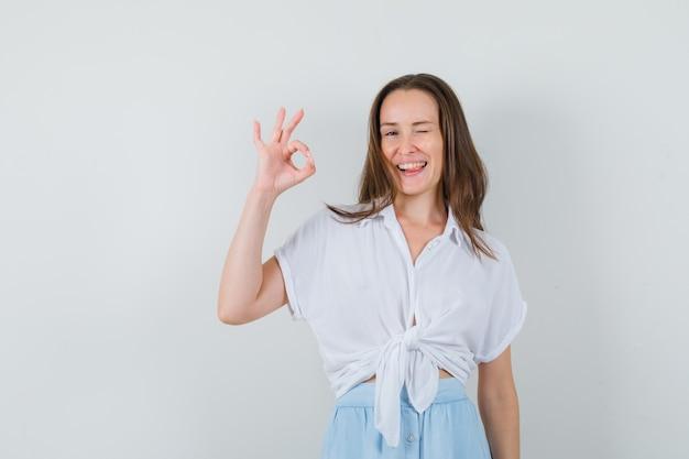 Jeune femme en chemisier blanc et jupe bleu clair montrant le signe correct et sticking tongue out et à la joyeuse