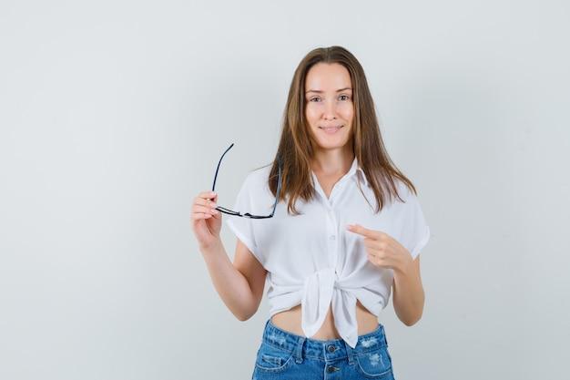 Jeune femme en chemisier blanc montrant des lunettes, vue de face.