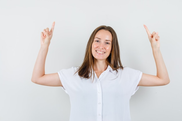 Jeune femme en chemisier blanc pointant vers le haut et à la joyeuse
