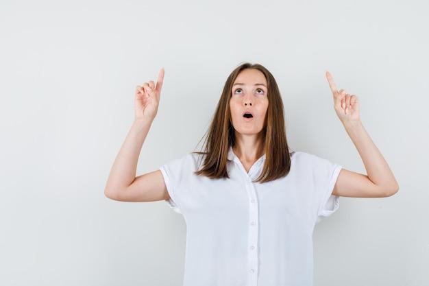 Jeune femme en chemisier blanc pointant vers le haut et à la stupéfaction