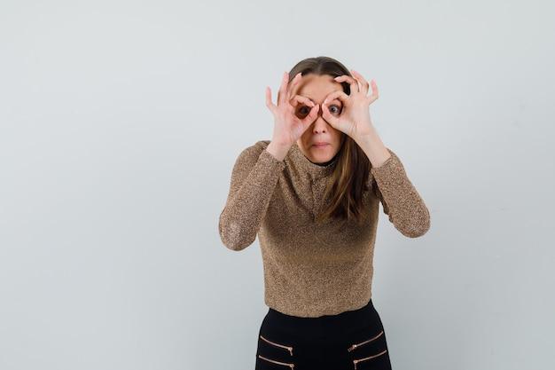 Jeune femme en chemisier doré montrant le geste binoculaire et à la vue de face, focalisée. espace pour le texte