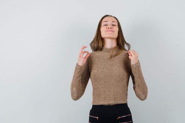 Jeune femme en chemisier doré pinçant son chemisier et à la confiance en soi