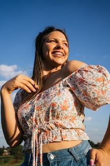Jeune femme en chemisier fleuri souriant à l'extérieur.