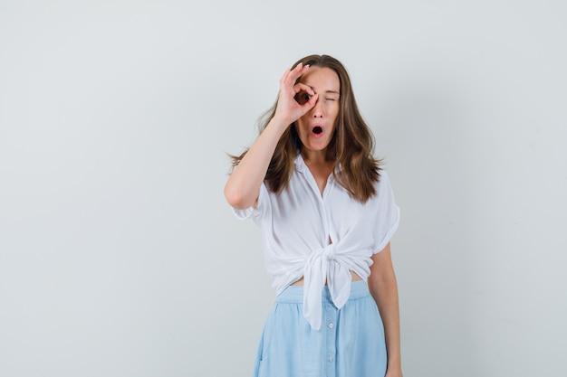 Jeune femme en chemisier et jupe montrant signe ok sur les yeux et à la curiosité