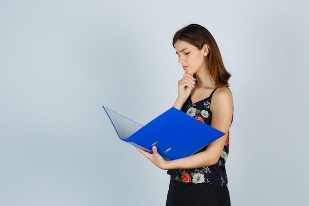 Jeune femme en chemisier, jupe regardant des documents dans un dossier et regardant pensive, vue de face.