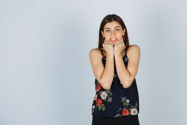 Jeune femme en chemisier, jupe tenant les poings sur le menton et l'air effrayé, vue de face.