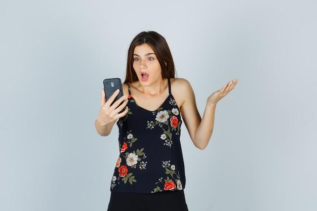 Jeune femme en chemisier levant la main tout en faisant un appel vidéo et l'air choquée, vue de face.