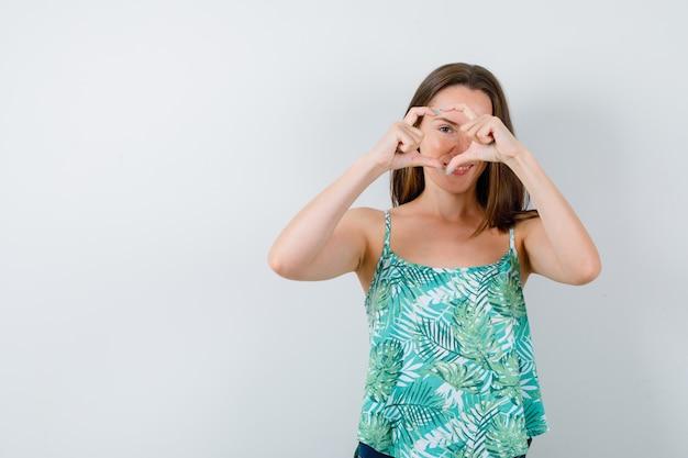 Jeune femme en chemisier montrant le geste du cœur et l'air mignon, vue de face.