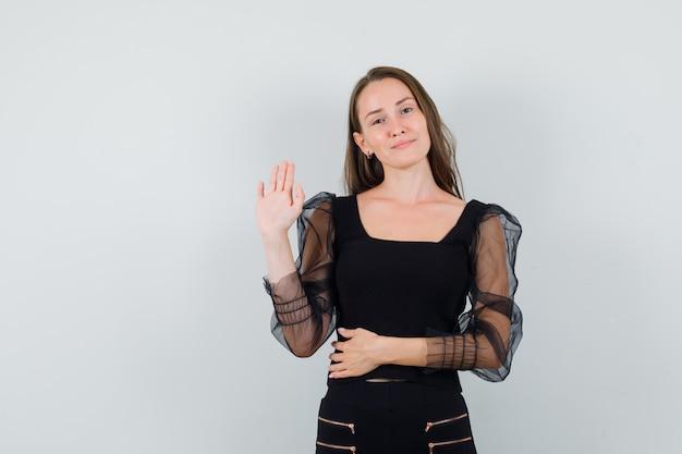 Jeune femme en chemisier noir montrant le geste d'adieu et à la recherche de calme