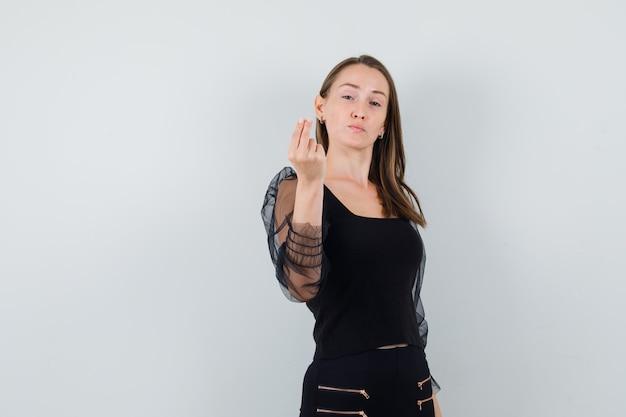 Jeune femme en chemisier noir et pantalon noir montrant le geste de l'argent et l'air confiant, vue de face.