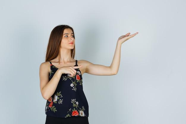 Jeune femme en chemisier pointant de côté tout en faisant un geste de bienvenue et en ayant l'air confiant, vue de face.