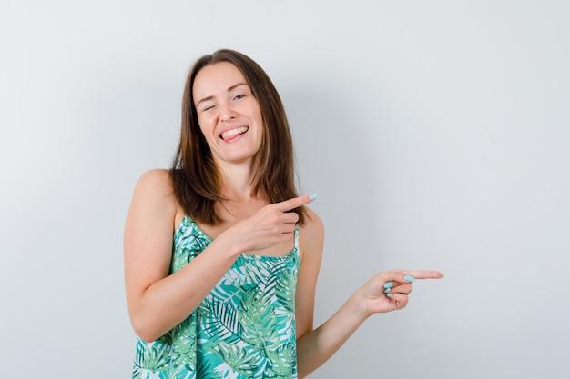 Jeune femme en chemisier pointant vers le côté droit et l'air heureux, vue de face.