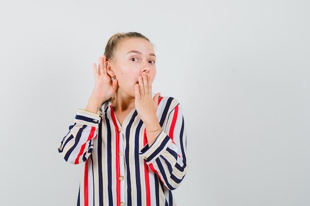 Jeune femme en chemisier rayé essayant d'entendre quelque chose et couvrant sa bouche avec les doigts et à la curiosité et la surprise