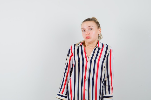 Jeune femme en chemisier rayé en haussant les épaules et à l'indécision