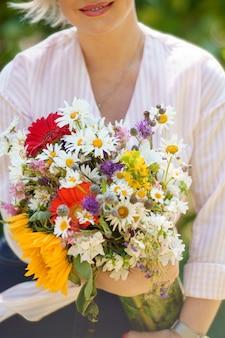 Une jeune femme en chemisier à rayures tient un bouquet de fleurs
