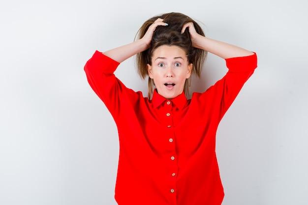 Jeune femme en chemisier rouge avec les cheveux dans les mains et à la demande, vue de face.