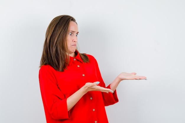 Jeune femme en chemisier rouge faisant semblant de montrer quelque chose et ayant l'air perplexe, vue de face.