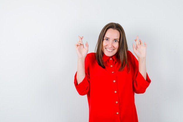 Jeune femme en chemisier rouge gardant les doigts croisés et regardant joyeux, vue de face.