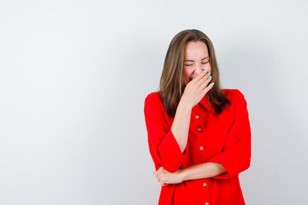 Jeune femme en chemisier rouge gardant la main sur la bouche et l'air heureux, vue de face.