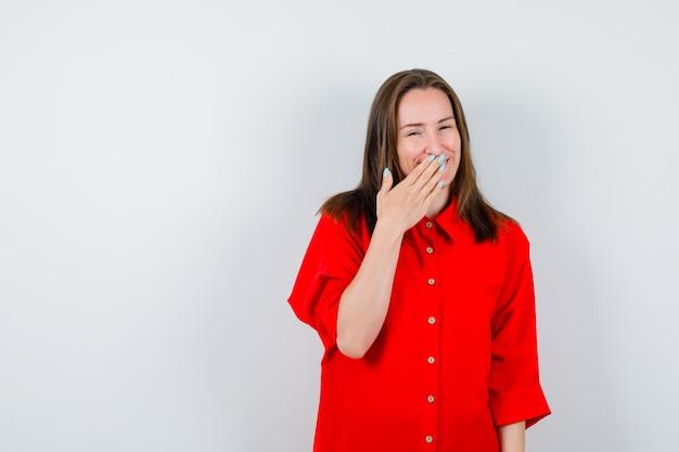 Jeune femme en chemisier rouge gardant la main sur la bouche et l'air joyeux, vue de face.