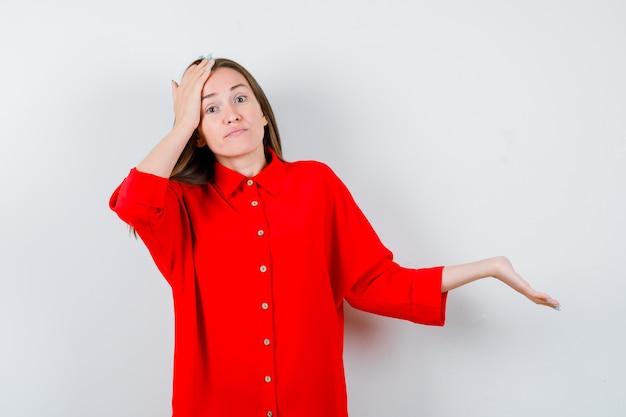 Jeune femme en chemisier rouge gardant la main sur la tête, écartant la paume et l'air confus, vue de face.