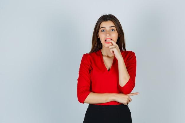 Jeune femme en chemisier rouge, jupe mordre le doigt tout en posant et à la recherche oublieux