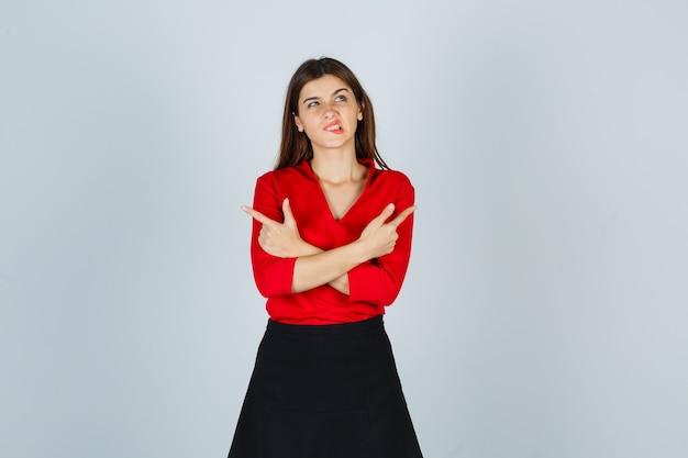 Jeune femme en chemisier rouge, jupe noire tenant deux bras croisés