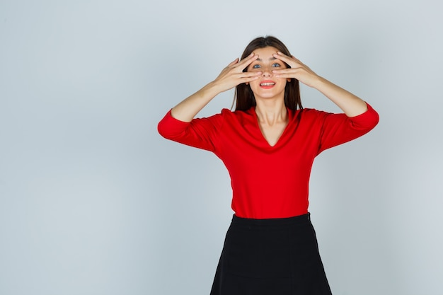 Jeune femme en chemisier rouge, jupe regardant à travers les doigts et à la jolie