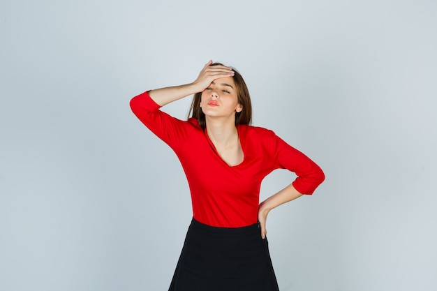Jeune femme en chemisier rouge, jupe tenant la main sur le front tout en gardant la main