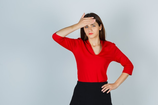 Jeune femme en chemisier rouge, jupe tenant la main sur le front