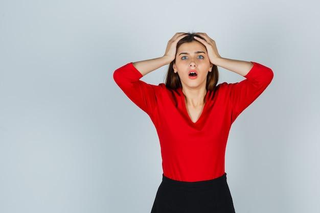 Jeune femme en chemisier rouge, jupe tenant les mains sur la tête et regardant oublieux
