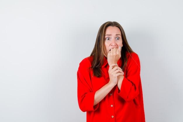 Jeune femme en chemisier rouge avec le poing sur la bouche et l'air effrayé, vue de face.