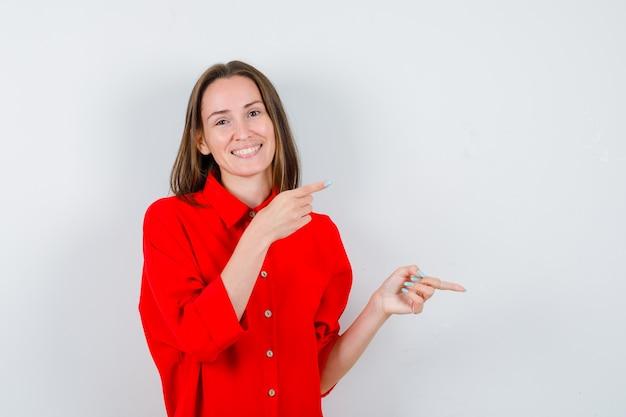 Jeune femme en chemisier rouge pointant vers la droite et l'air heureux, vue de face.
