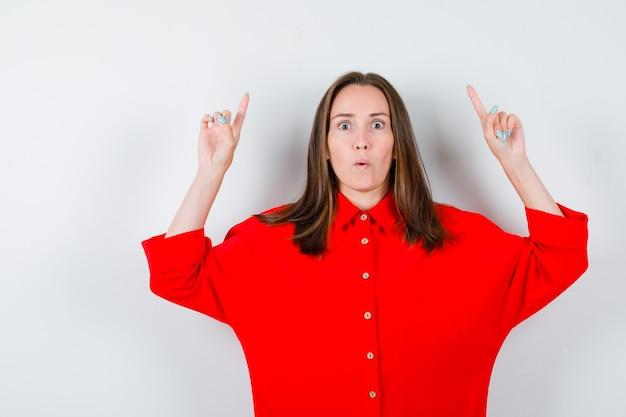 Jeune femme en chemisier rouge pointant vers le haut avec les doigts et l'air choqué, vue de face.
