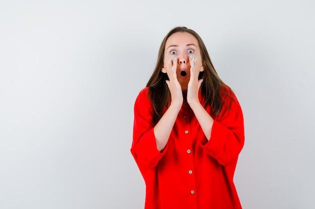 Jeune femme en chemisier rouge racontant le secret et semblant choquée, vue de face.