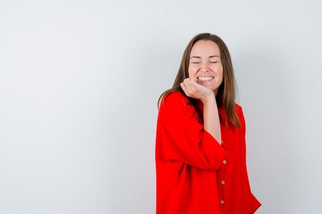 Jeune femme en chemisier rouge s'appuyant sur le menton et l'air heureux, vue de face.