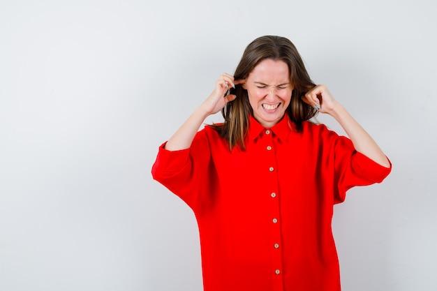 Jeune femme en chemisier rouge se branchant les oreilles avec les doigts et l'air ennuyé, vue de face.