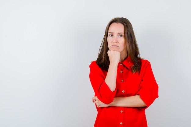 Jeune femme en chemisier rouge se penchant le menton sur le poing et à la perplexité, vue de face.