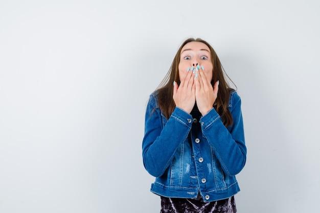 Jeune femme en chemisier, veste en jean avec les mains sur la bouche pour envoyer un baiser et l'air mignon, vue de face.