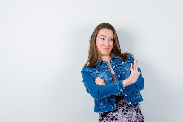 Jeune femme en chemisier, veste en jean montrant un geste d'arrêt et l'air confiant, vue de face.